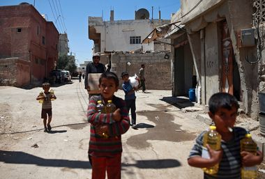 Syrian children and a man are seen carrying food aid in Douma, near Damascus, Syria August 6, 2017. REUTERS/Bassam Khabieh - RC1CABB2AAB0