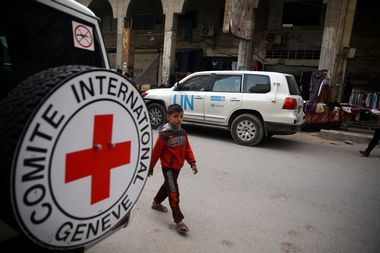 A Syrian child is seen walking near International Red Cross vehicle in the rebel-held city of Douma, in the eastern Damascus suburb of Ghouta, Syria November 12, 2017. REUTERS/Bassam Khabieh - RC1BF4735420