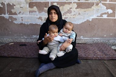 Six-month-old twins Safa and Marwa, who suffer from malnutrition, are held by their mother in the Hazzeh area, in the eastern Damascus suburb of Ghouta, Syria, October 25, 2017. REUTERS/Bassam Khabieh SEARCH