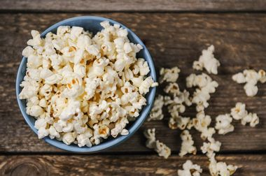 Popcorn in a blue bowl on wooden table