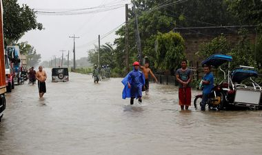 Stranded commuters stand on a partially flooded road after Typhoon Mangkhut hit the main island of Luzon, in Carranglan, Nueva Ecija, Philippines, September 15, 2018. REUTERS/Erik De Castro
