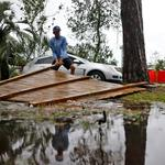 Joseph Howat clears a damaged fence by Hurricane Michael at his business in Panama City Beach