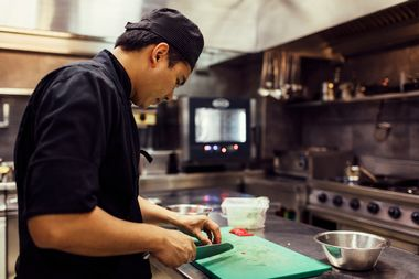 Chef working in his kitchen in restaurant. He is preparing asian food, cutting vegetable. This is real chef not model.