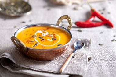 Pumpkin cream-soup with chili and seeds in a copper bowl