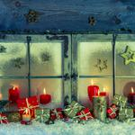 Old wooden window decorated for christmas with red candles and p
