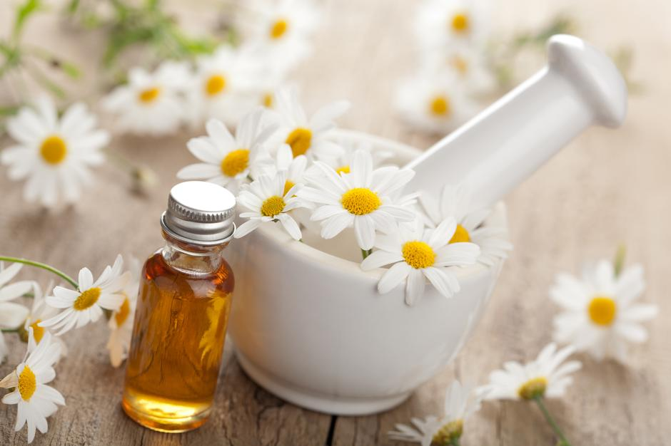 essential oil and camomile flowers in mortar | Autor: OlgaMiltsova