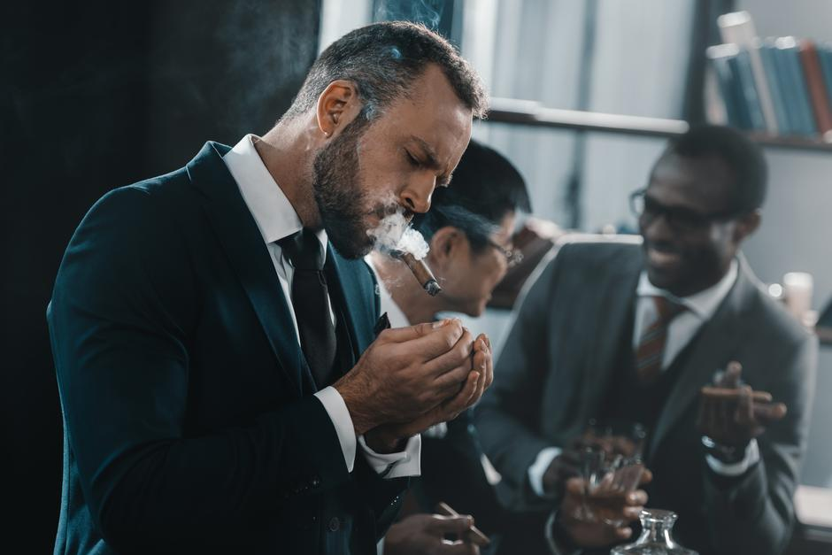 businessman smoking cigar with multicultural business team   Autor: Dreamstime