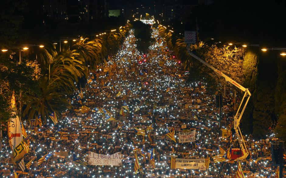 Protestors hold the light of their mobiles during a demonstration called by pro-independence associations asking for the release of jailed Catalan activists and leaders in Barcelona | Autor: ALBERT GEA
