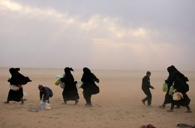 Women walk with their belongings near the village of Baghouz, Deir Al Zor province, Syria February 26, 2019. REUTERS/Rodi Said TPX IMAGES OF THE DAY