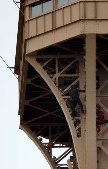 An unidentified man climbs the Eiffel Tower, which had to be evacuated, next to a Paris fire brigade specialist in Paris, France, May 20, 2019. REUTERS/Charles Platiau