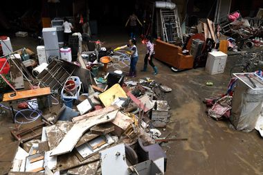 Residents clean up their belongings after their houses were hit by flood following heavy rainfall in Sanming, Fujian province, China June 11, 2019. Picture taken June 11, 2019. Zhang Bin/CNS via REUTERS ATTENTION EDITORS - THIS IMAGE WAS PROVIDED BY A THIRD PARTY. CHINA OUT.