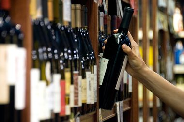 A woman's hand reaches out to select a bottle of red wine from the shelf of a wine shop