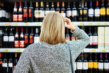 Girl chooses wine in a supermarket