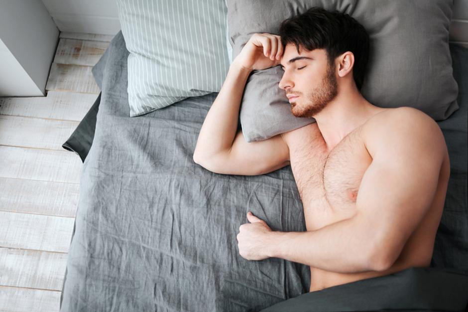 Single young muscular man sleeping in bed. He hold head on pillow. Young man is naked. Lower part of body covered with grey blanket. | Autor: Dreamstime