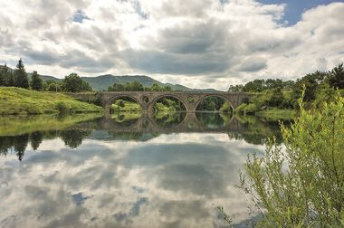 Nature and landscape photo of Kosinj and Lika river in Croatia. Beautiful outdoor on warm summer day. Calm, peaceful and colorful image. Nice architecture of bridge over water.