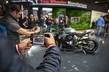 Attendees take photographs of the AMB 001 motorcycle on display at the Aston Martin Lagonda Global Holdings Plc stand at the EICMA Motorcycle Show in Milan, Italy, on Nov. 6, 2019. Aston Martin debuted the 180-horsepower motorcycle, coming with a V-twin, turbo-charged engine, made in partnership with Brough Superior at the show. Photographer: Camilla Cerea/Bloomberg via Getty Images